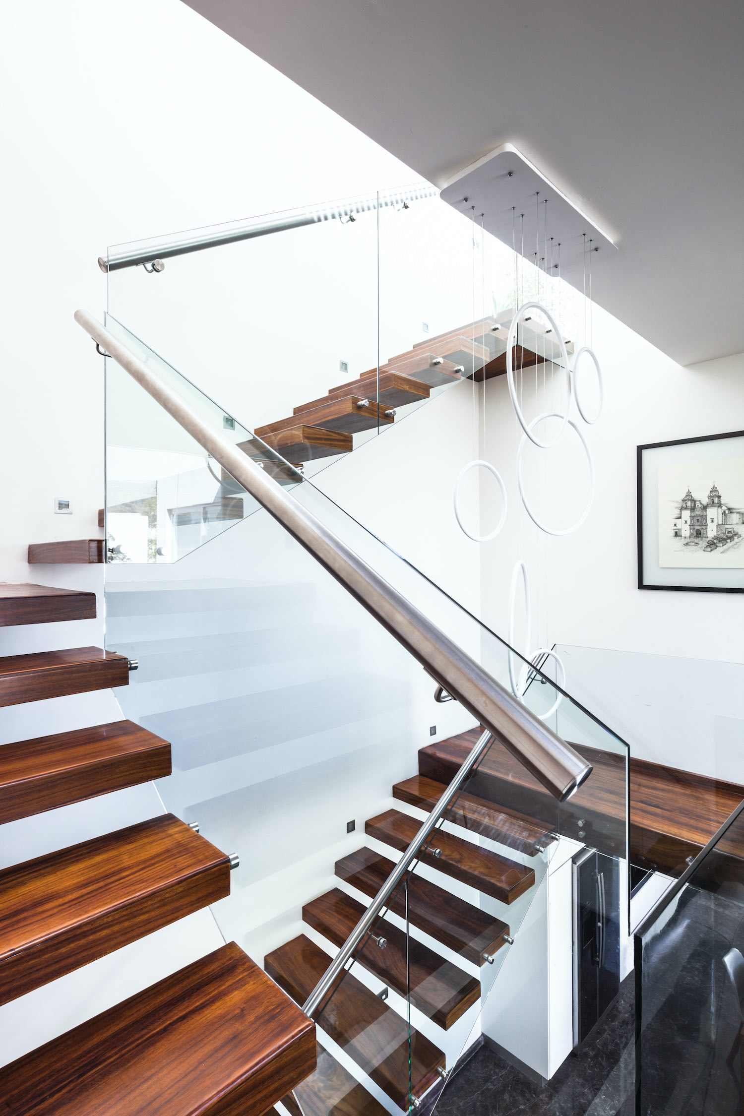 staircase with wooden stapes and glass handrail