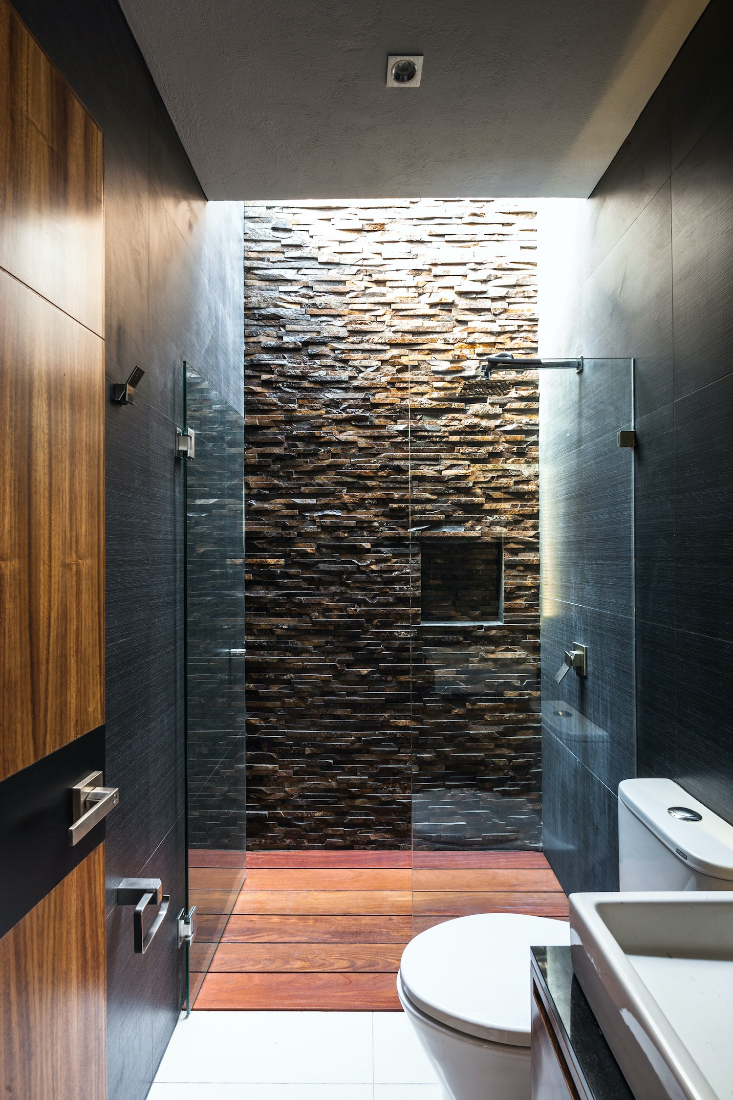 bathroom with wooden parquet floor and stone wall