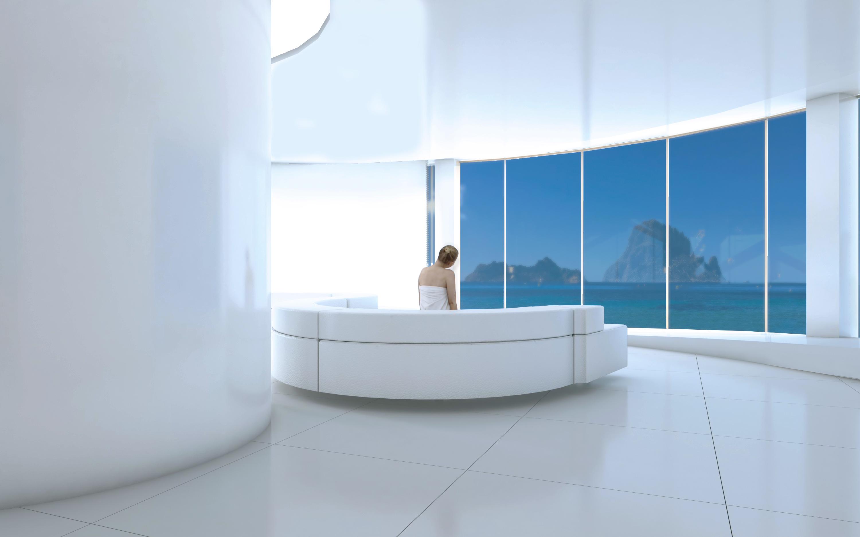 woman sitting on circular white sofa staring at the sea through window
