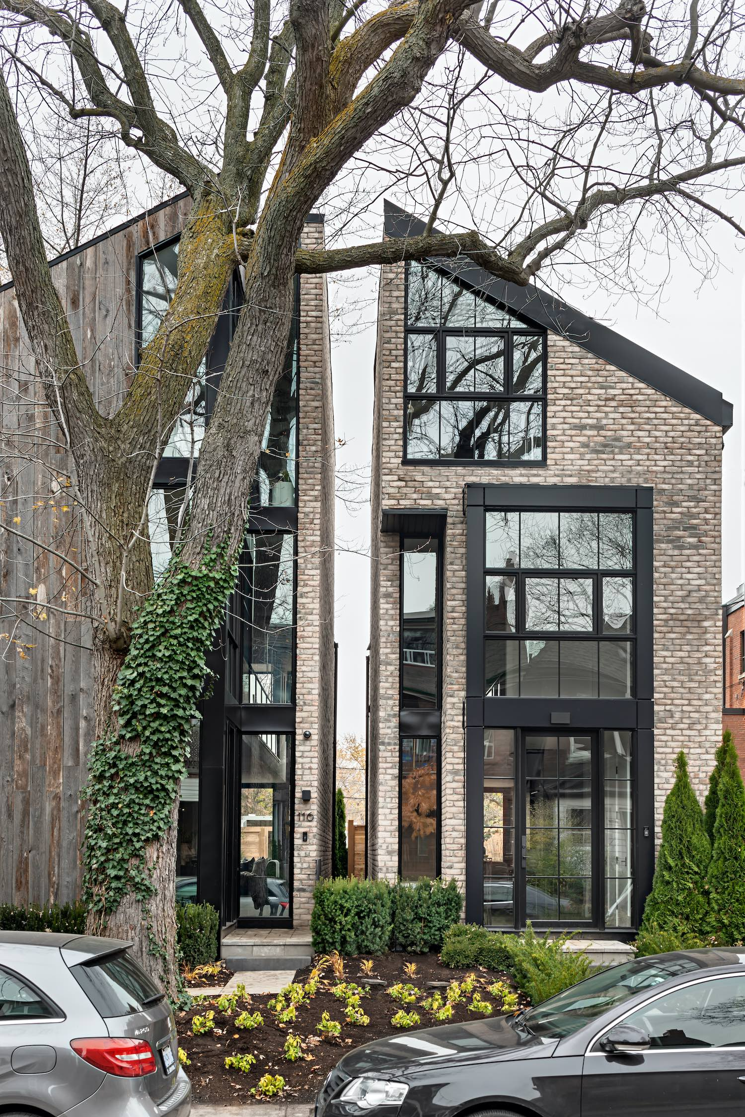 semi detached house with brick facade and a big tree in front