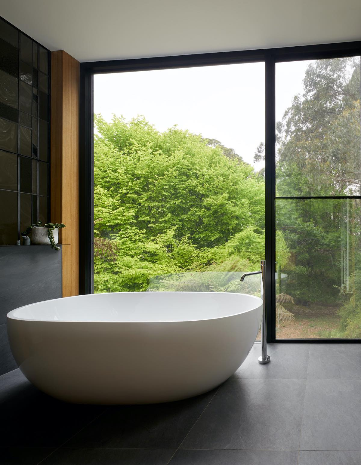 a white oval shaped bathtub in bathroom having spectacular view of nature through glass window
