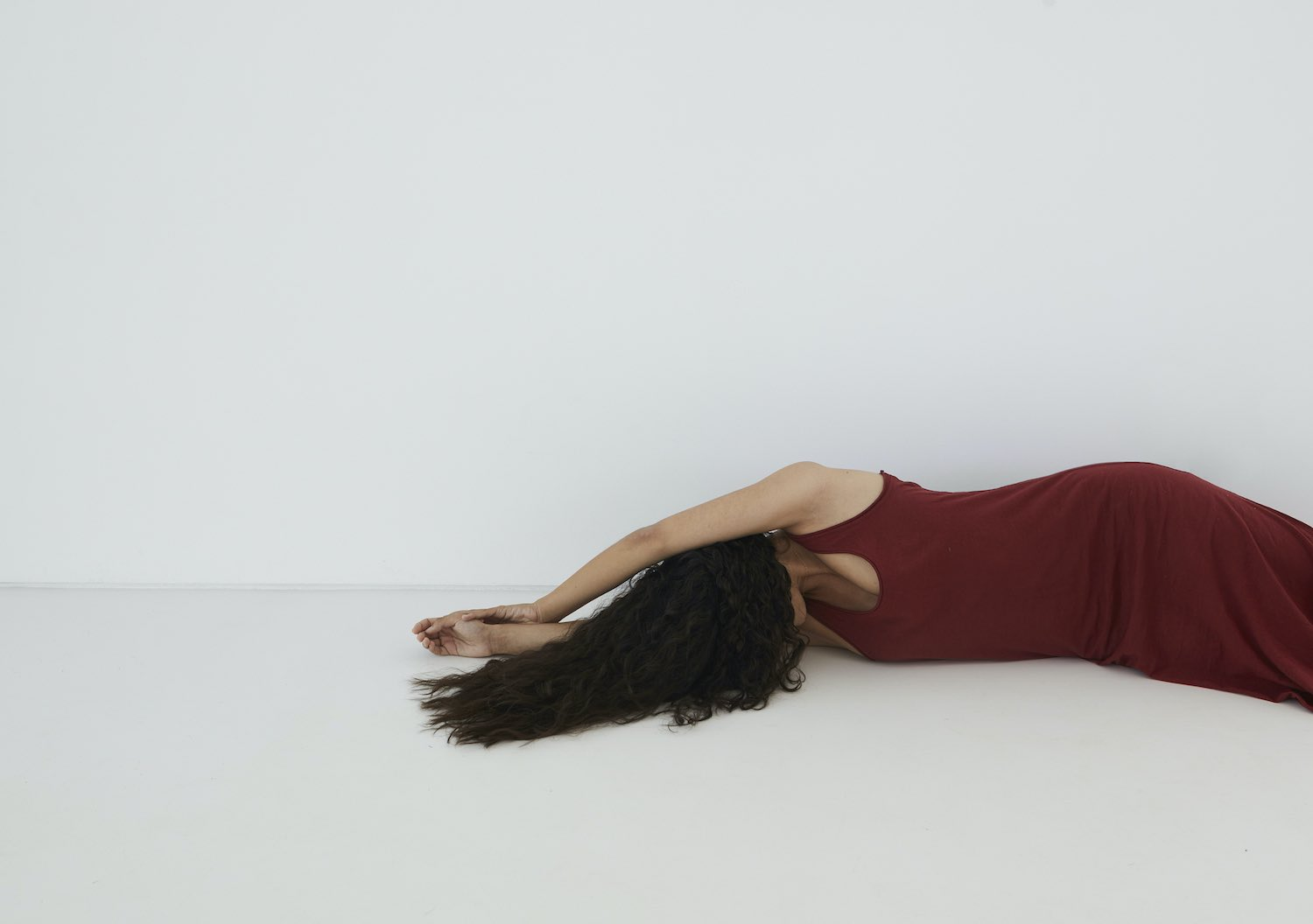 girl with long hair and red dress lying down on floor