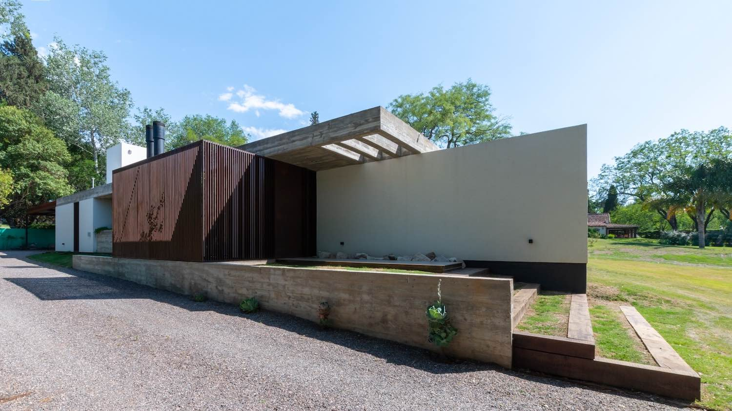 concrete, wood and metal used as the exterior material for this house