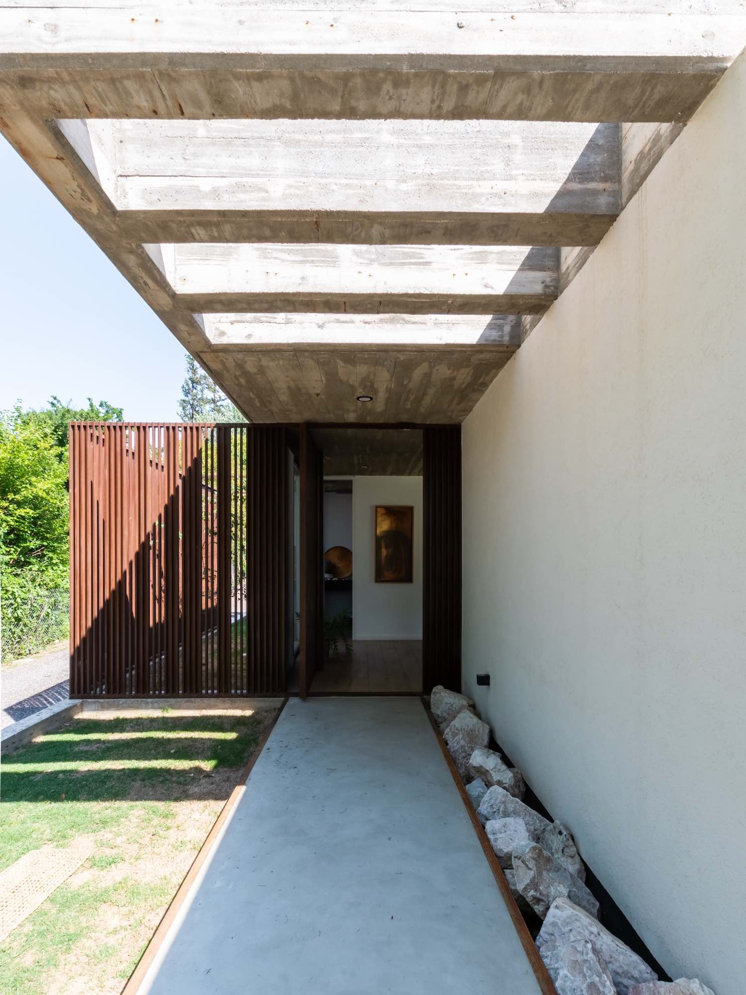 concrete cantilever covering the entrance door