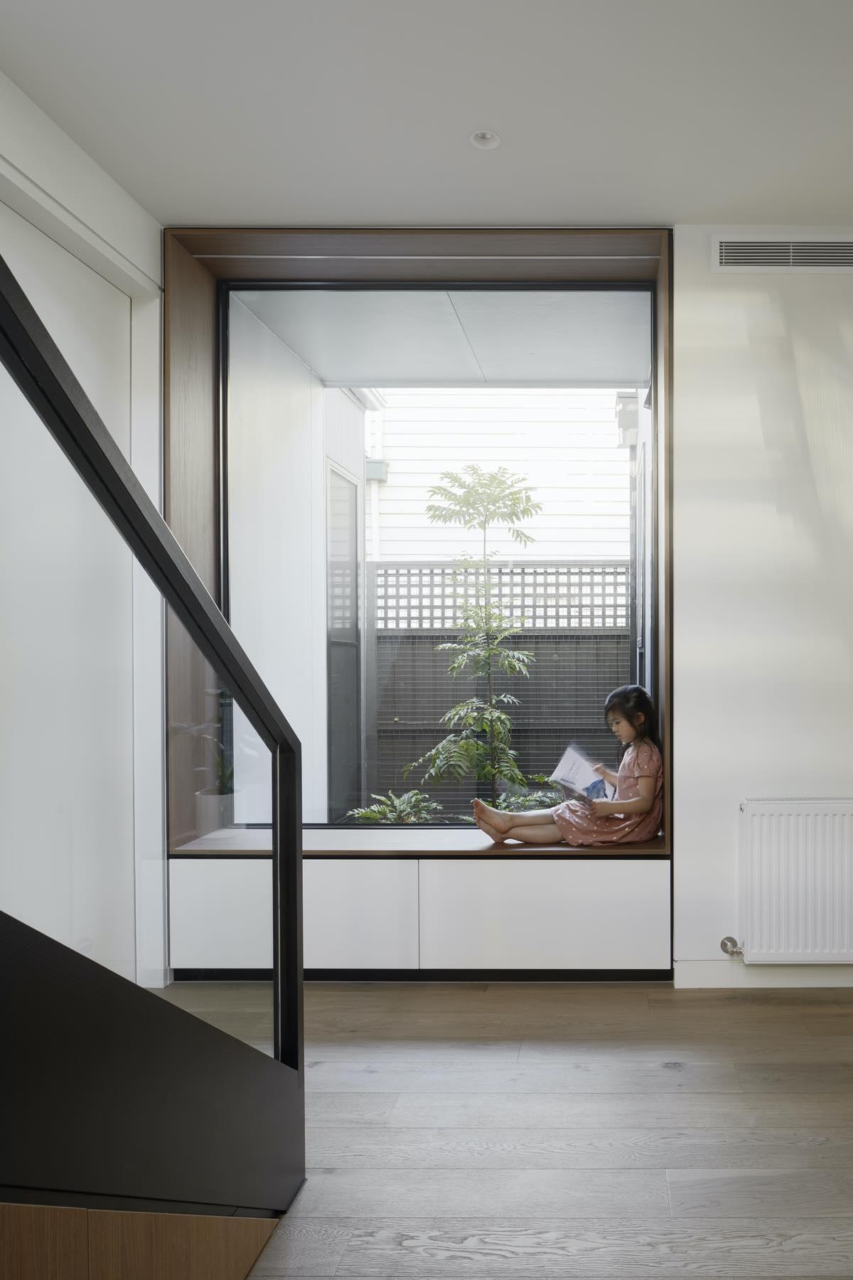 kid sitting beside a large vertical window
