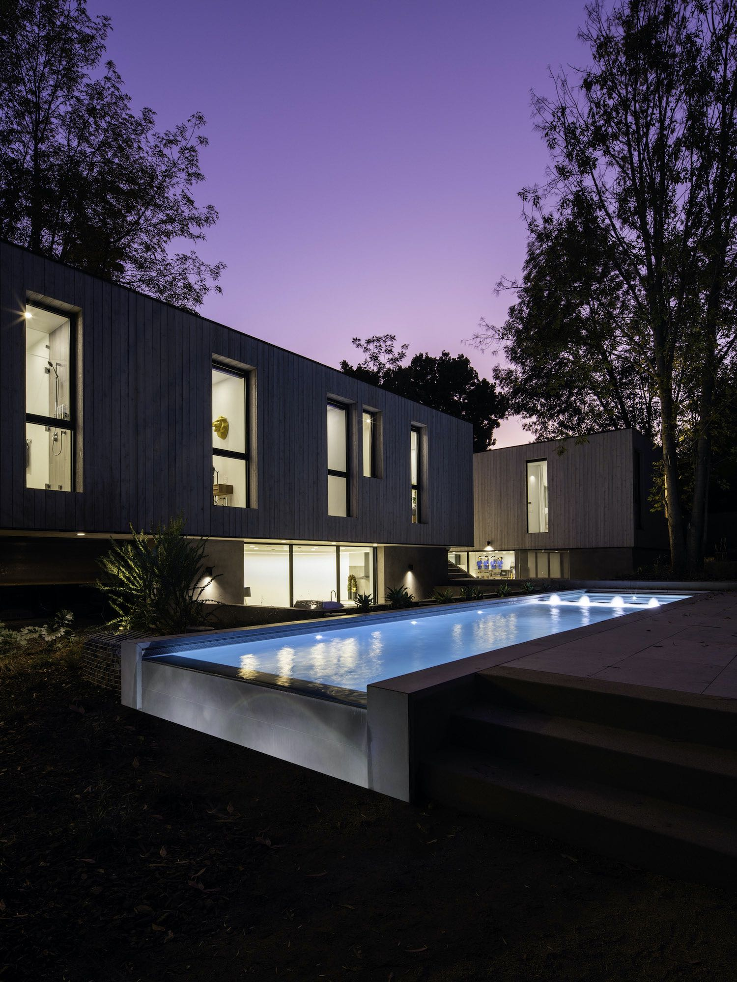 house with pool illuminated at night