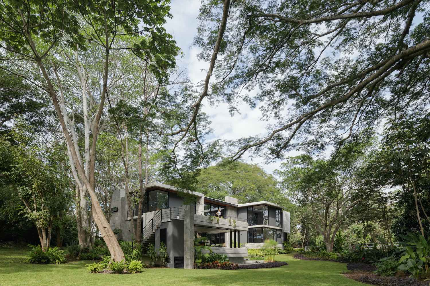 a concrete house located among trees in a jungle in Mexico