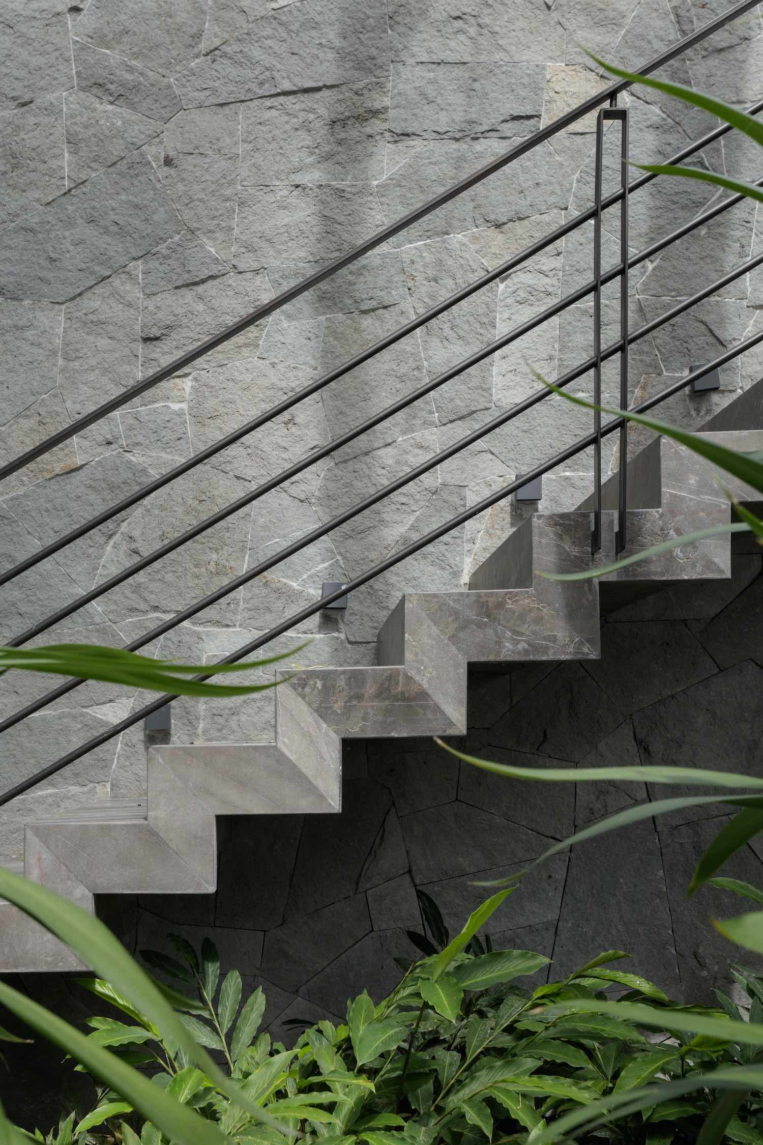 modern concrete staircase with stone wall
