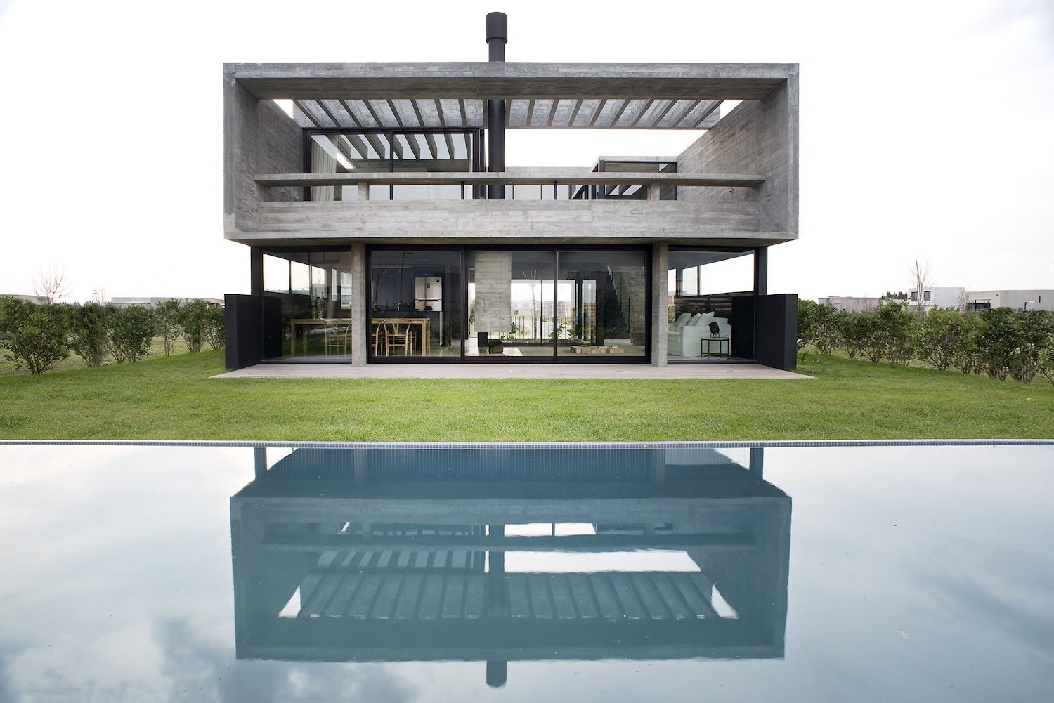 reflection of the concrete house in the pool