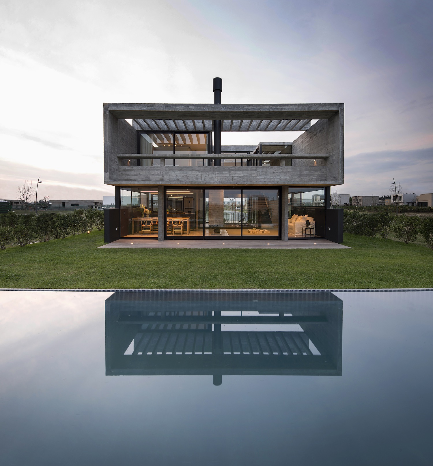 house with illumination reflected at swimming pool