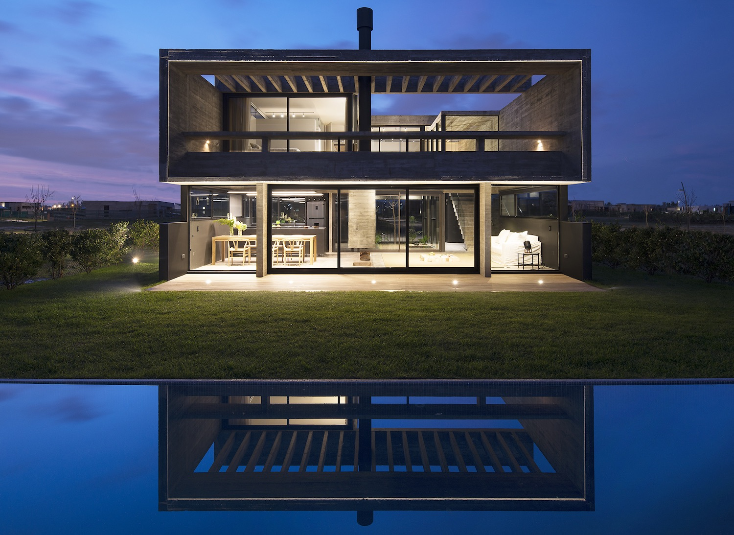 concrete house with illumination at night reflected at pool