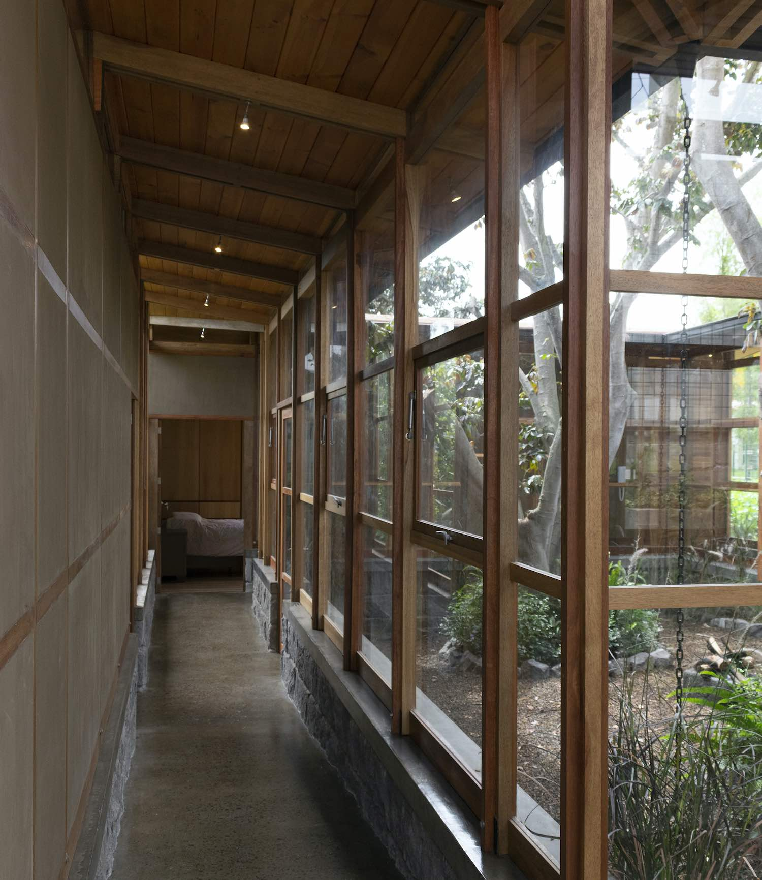 corridor with large wooden windows and patio view