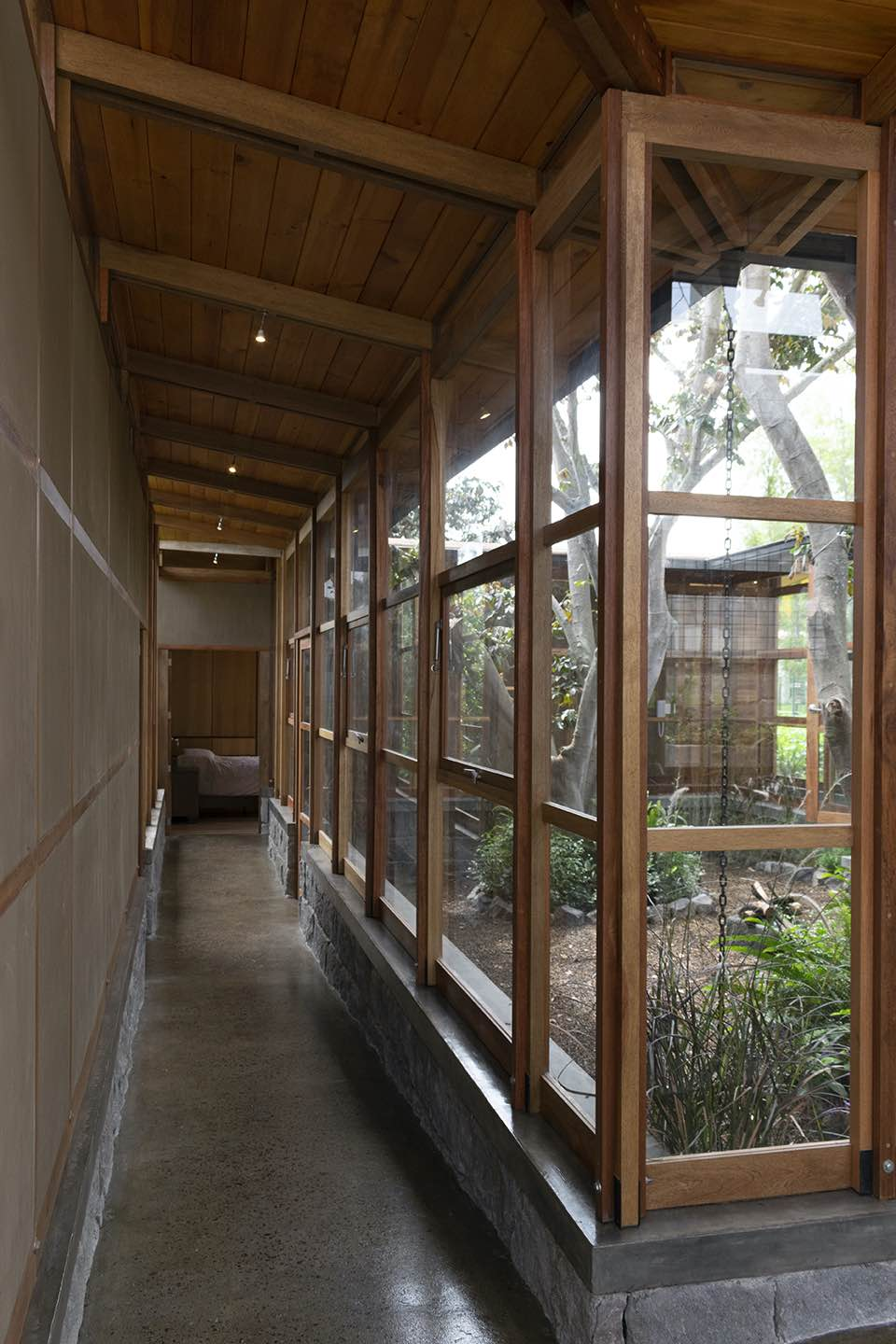 a corridor connecting living area to bedroom with large windows
