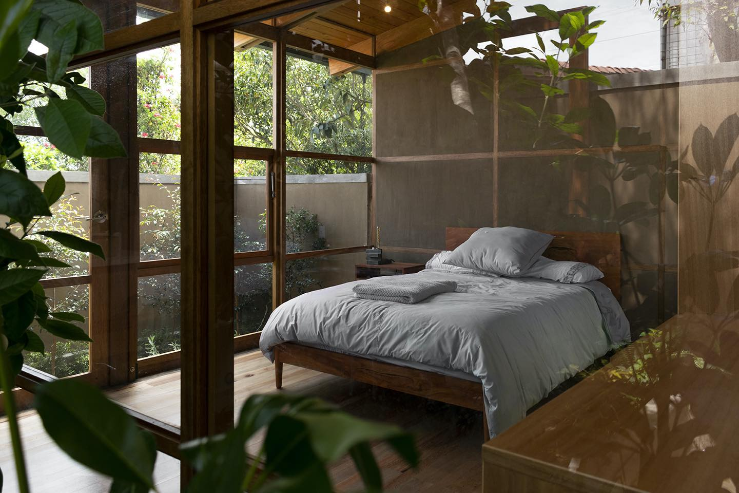 master bedroom with glass window letting the natural light enter the room