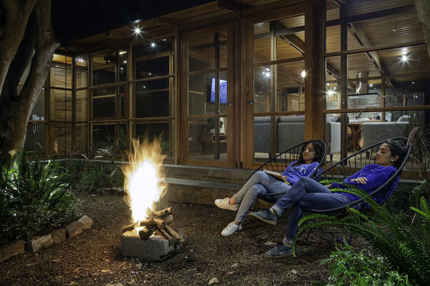 two women with blue sweaters sitting by fire side at the garden