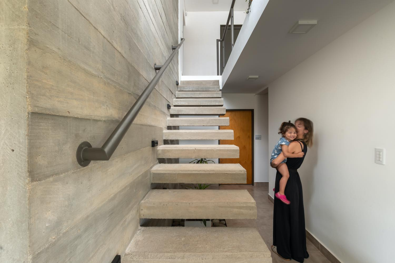 a kid hugging her mother nearby stairs