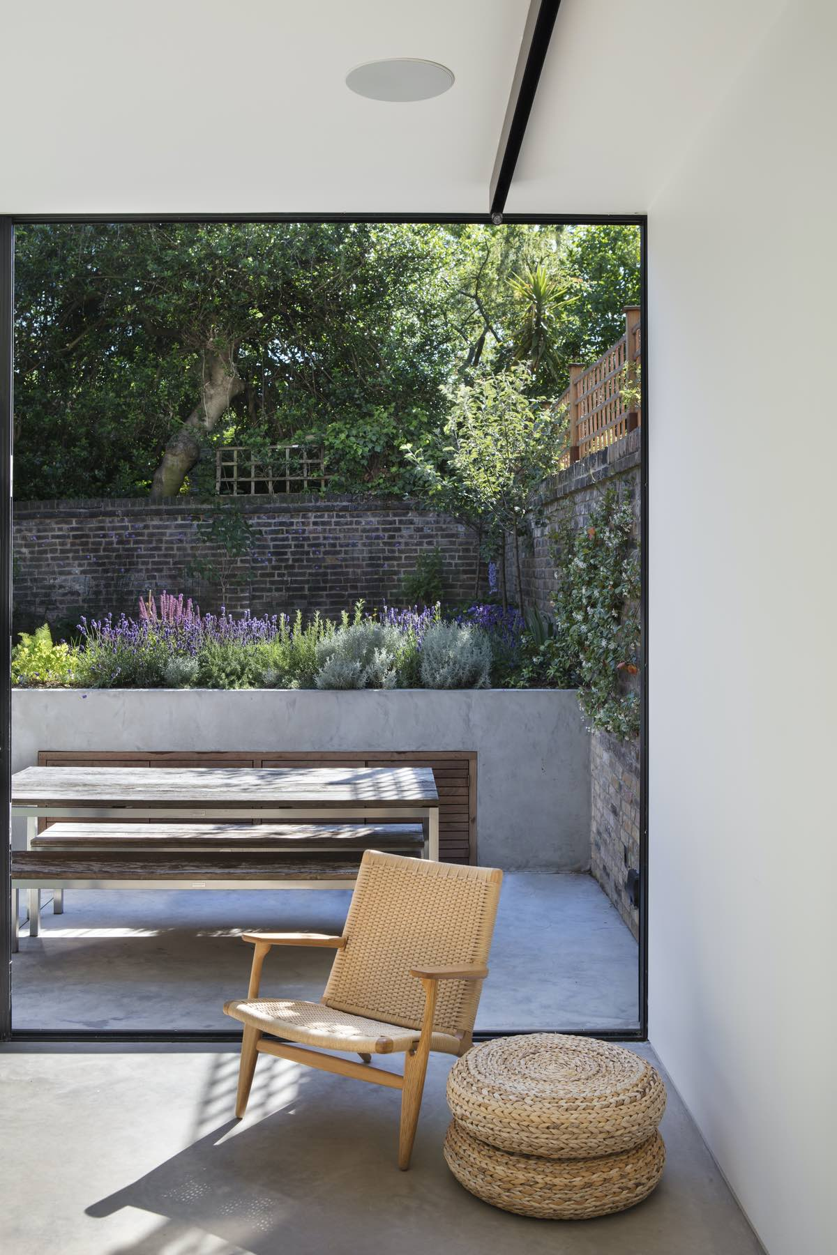 a modern wooden chair in the sitting area with beautiful garden view