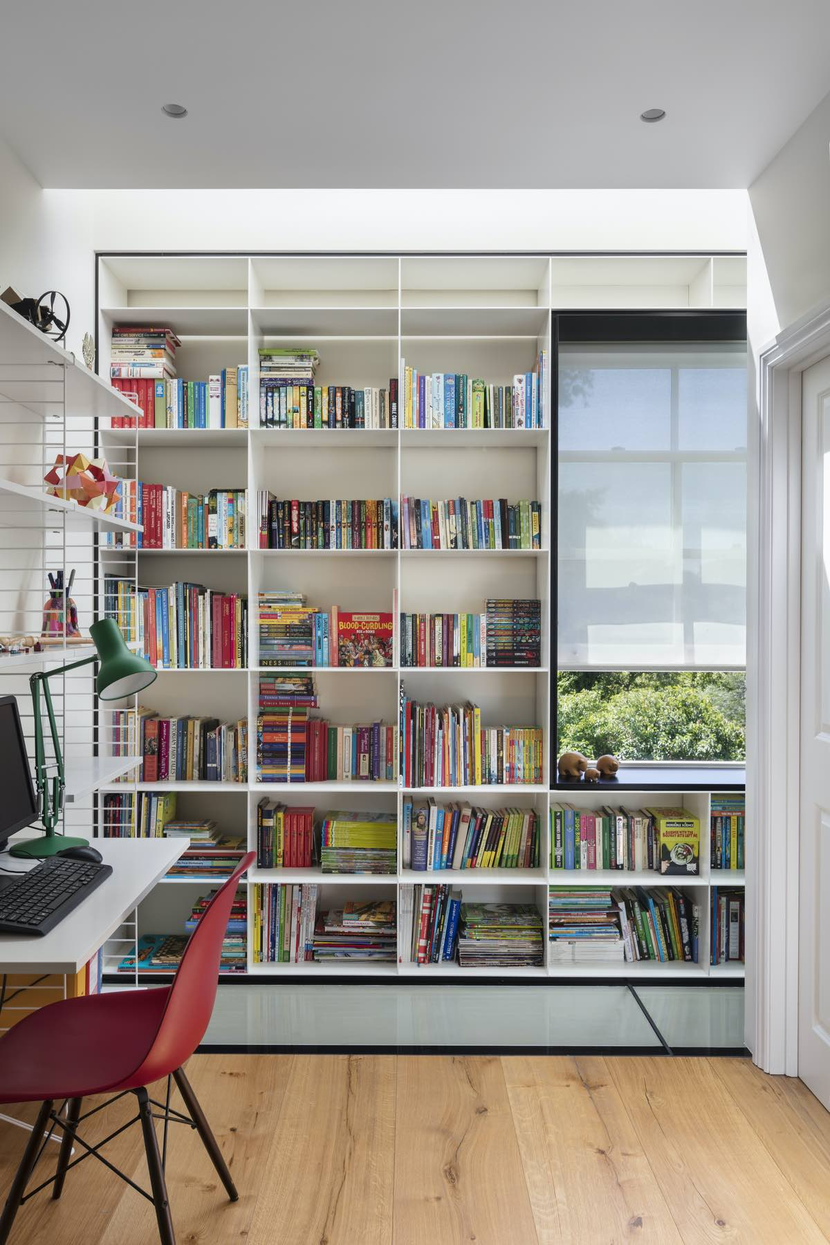 an office room with big white bookshelf