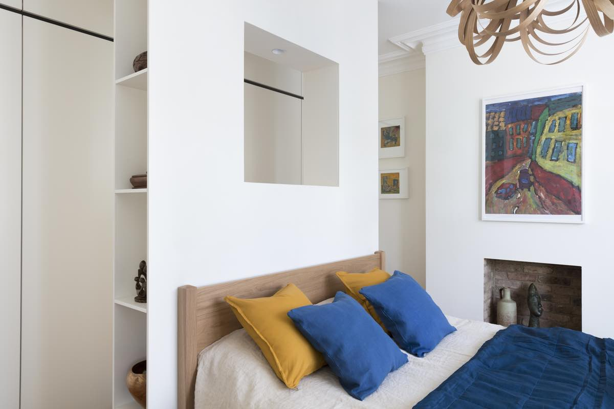 a bedroom with blue and yellow pillows