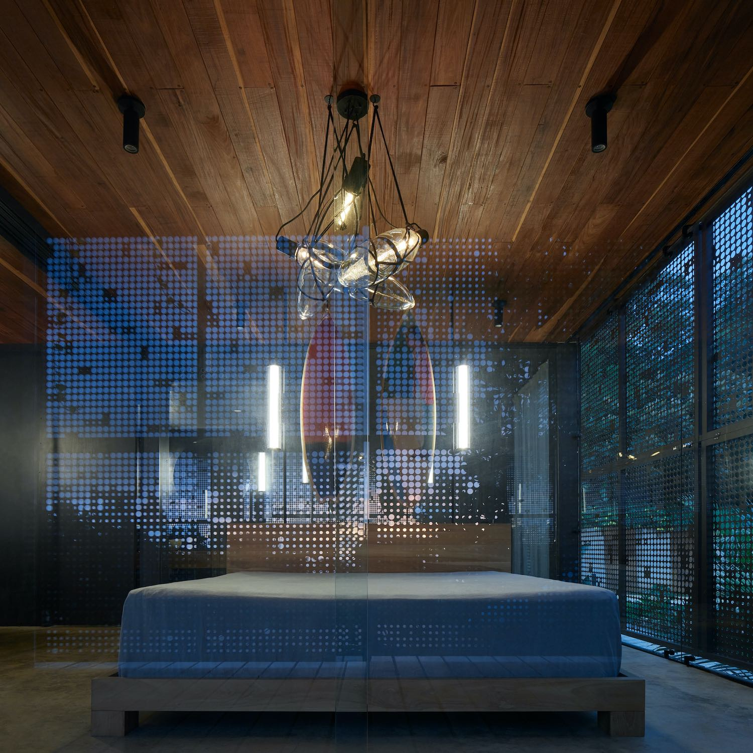 bedroom at night with illumination can be seen through glass walls