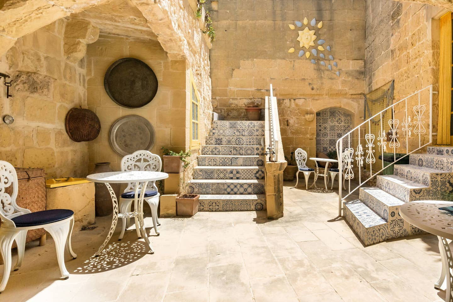 white metallic chairs and table at the house yard near staircase