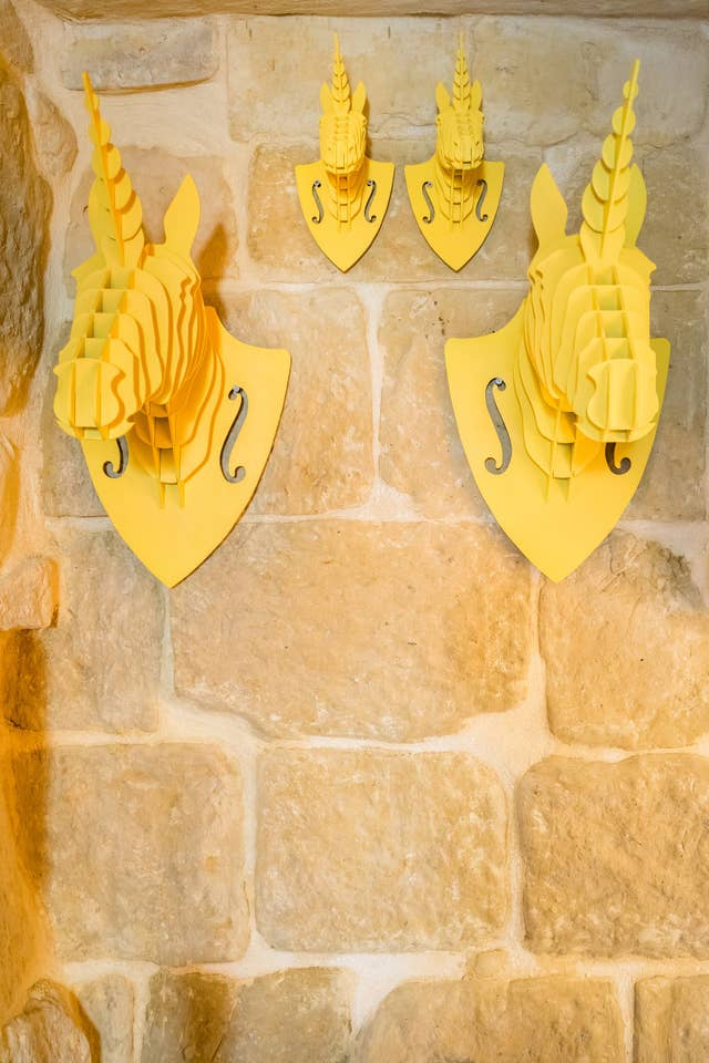 yellow animal sculptures hanged on the stone wall