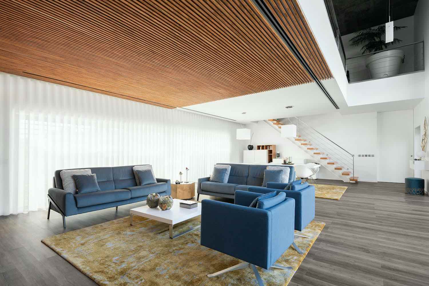 a living area with wooden ceiling and blue sofa