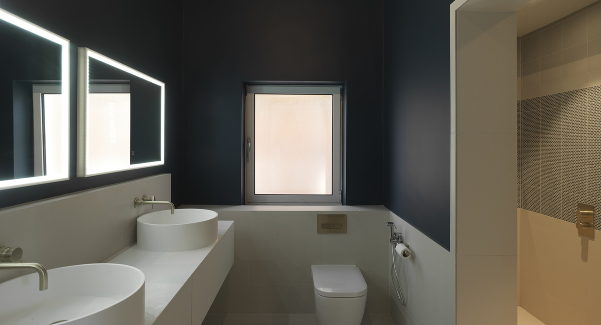 a bathroom with led lighting at the frame of mirrors