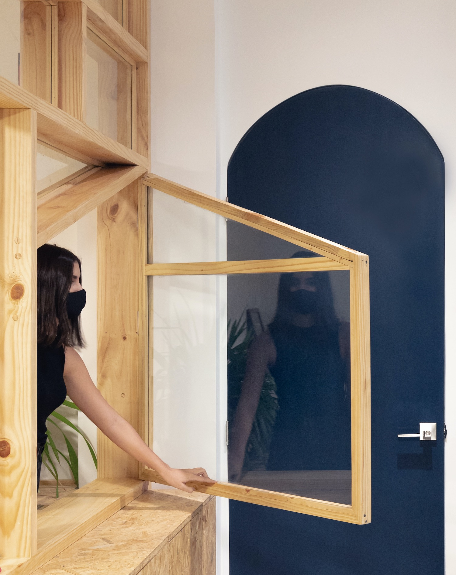 beautiful girl wearing black mask opening window