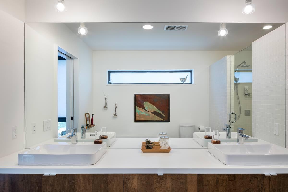 huge mirror and white washing basins