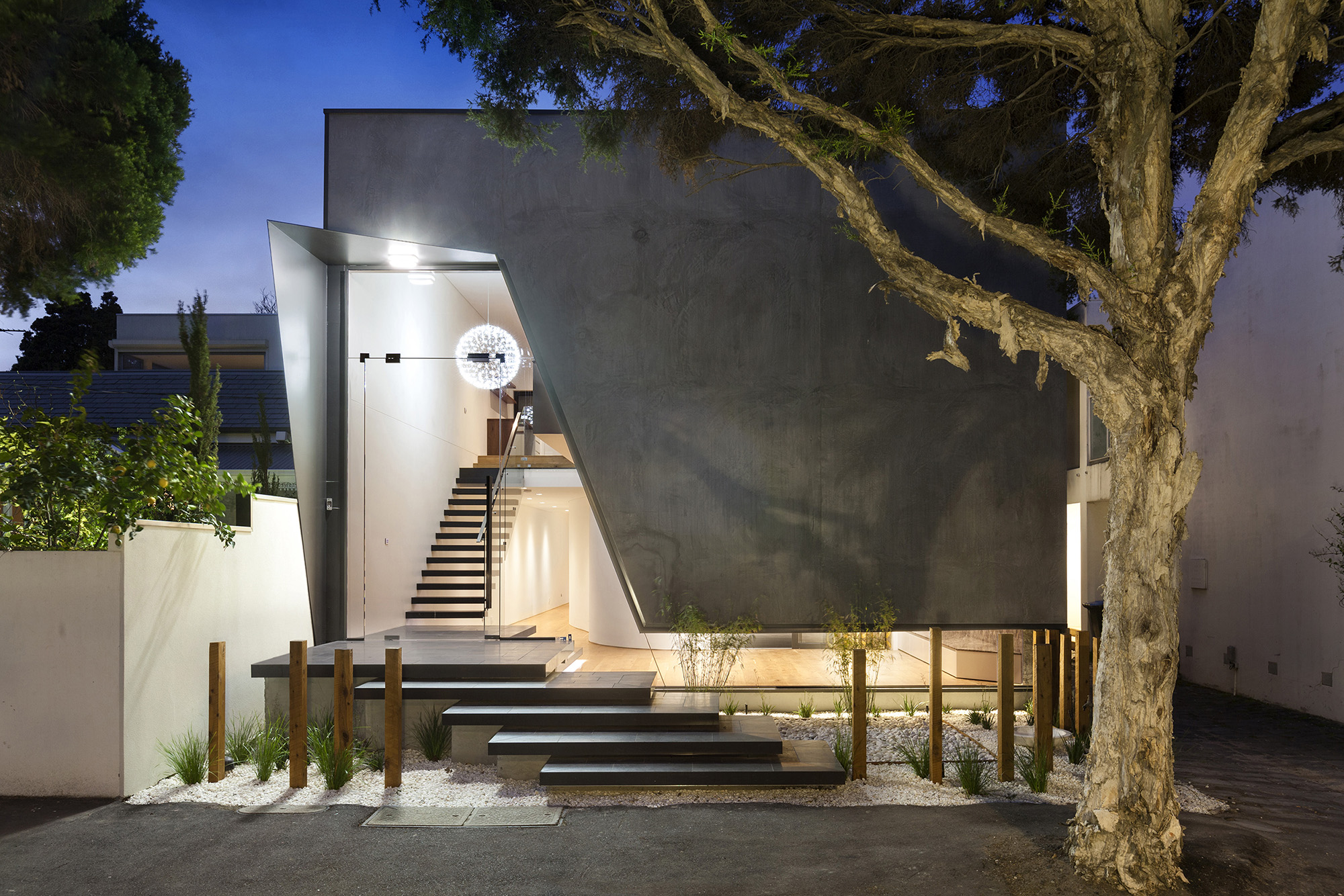 house entrance with stepped staircase and a tree in front