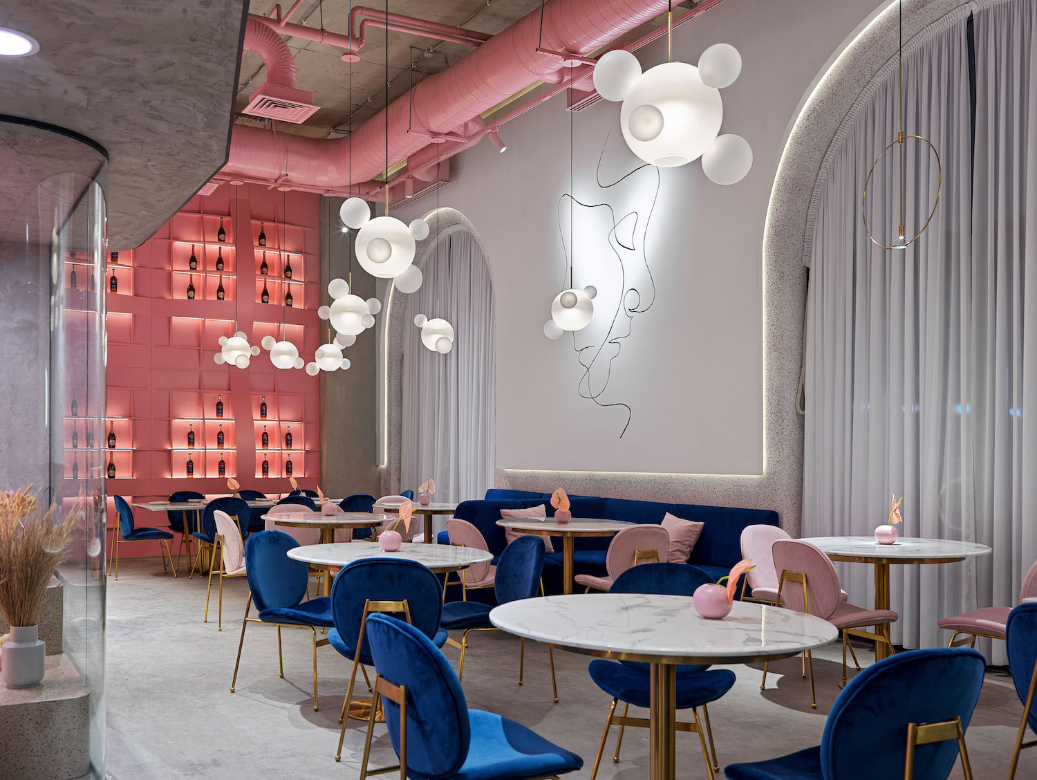 restaurant with dining table, chairs and pink pipes in the ceiling