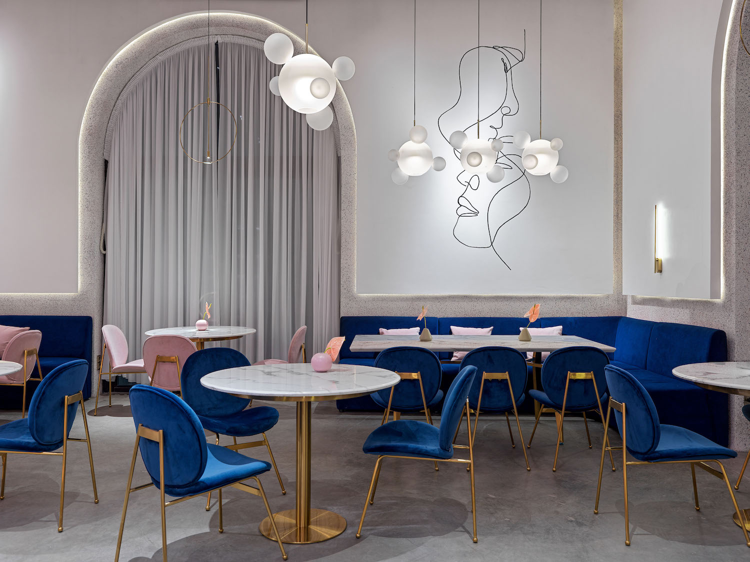 circular pendant lamps hanged over circular tables and blue chairs