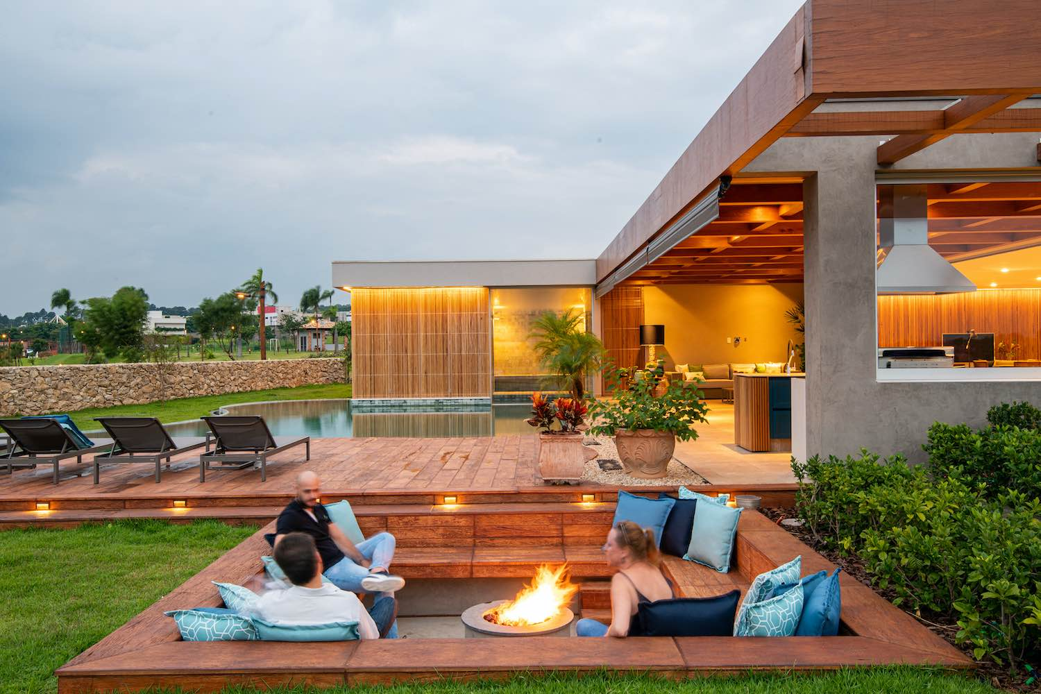 family sitting by fire at outdoor living space with pool view
