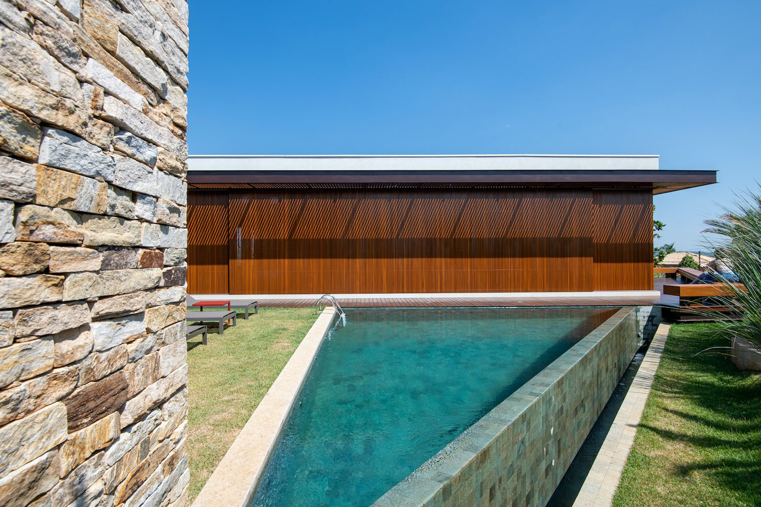 house with stone wall near the pool