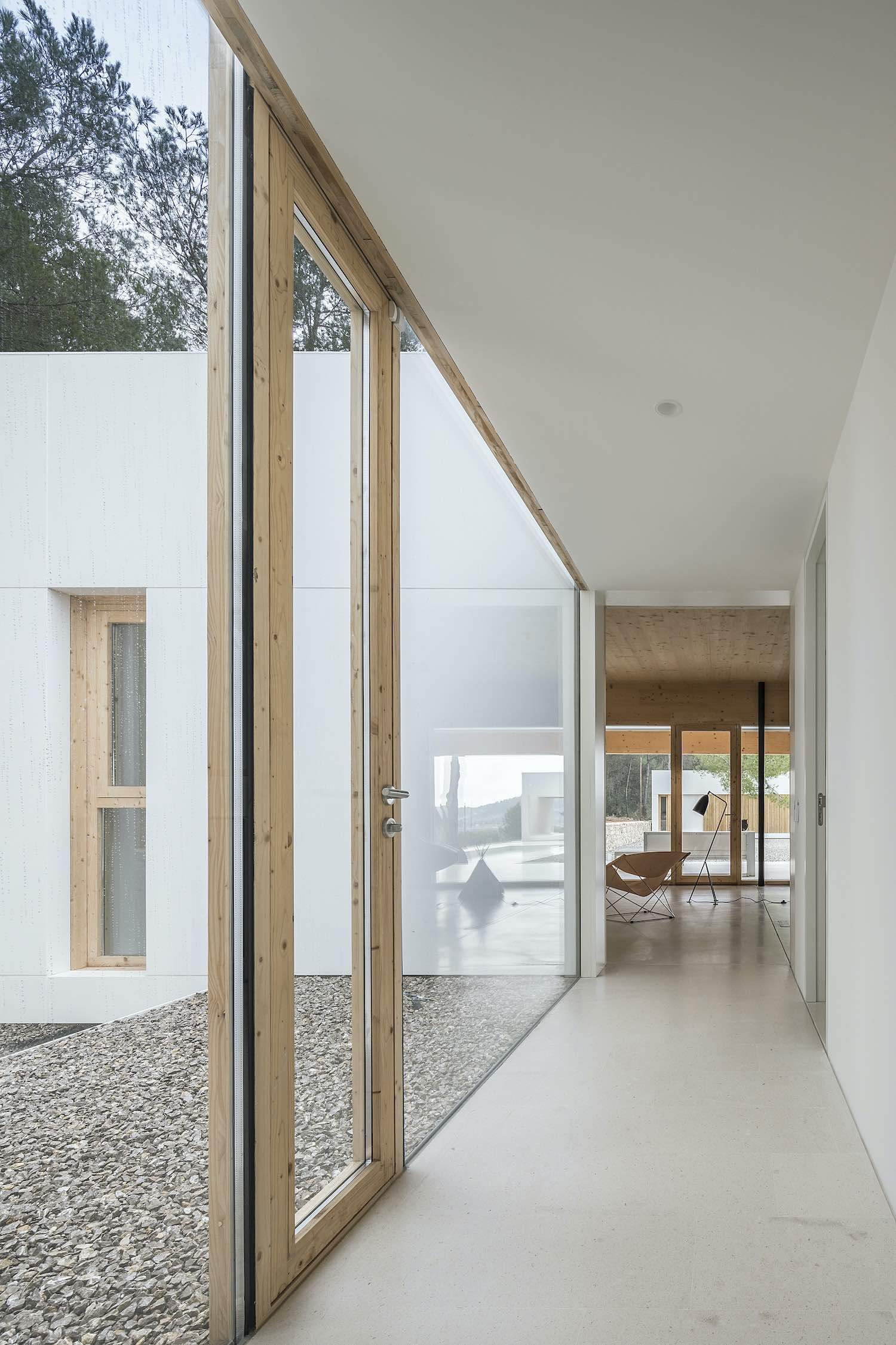 the sun light enters the house through large glass windows