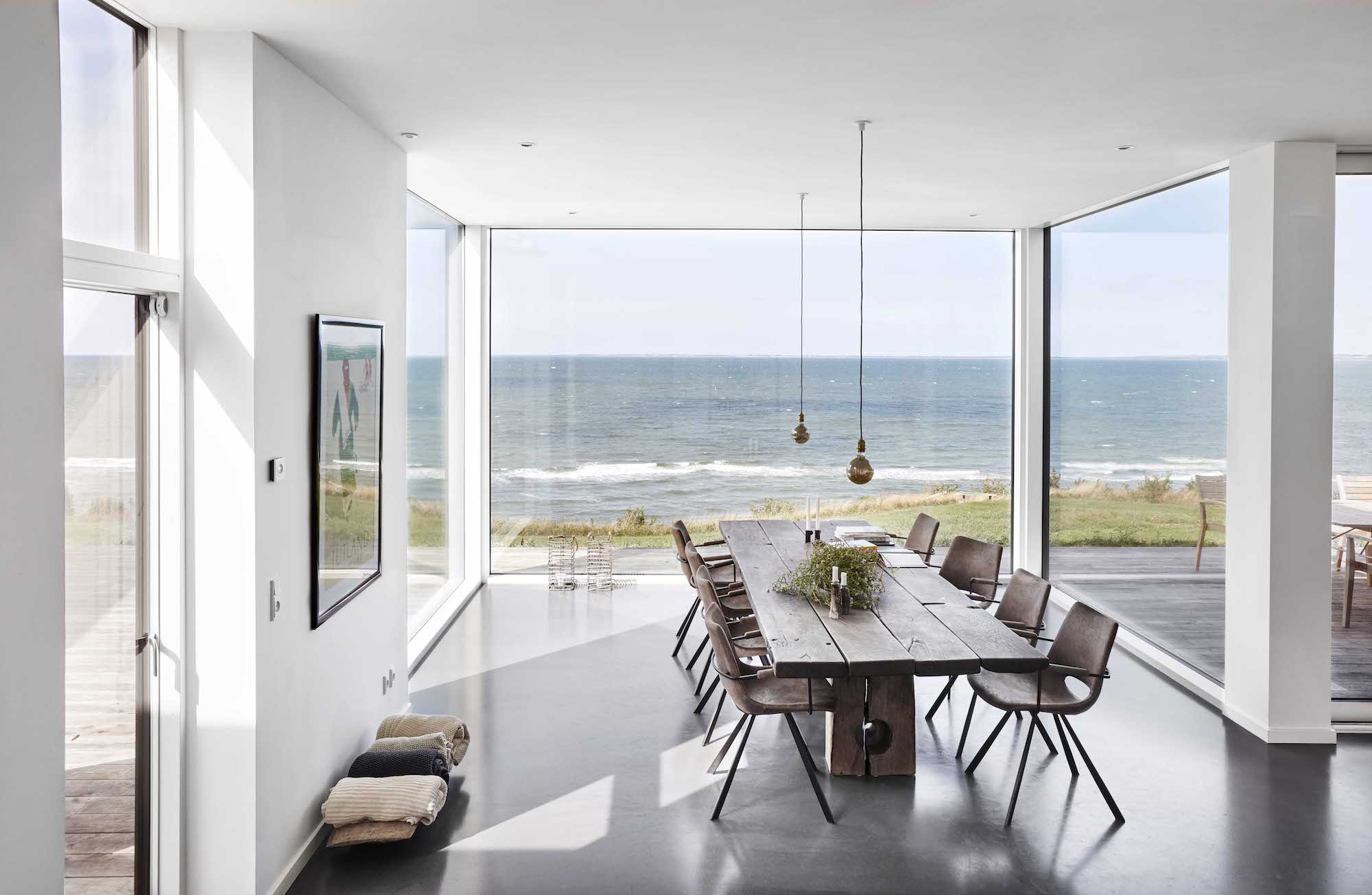 wooden dining table with large windows to see the sea view