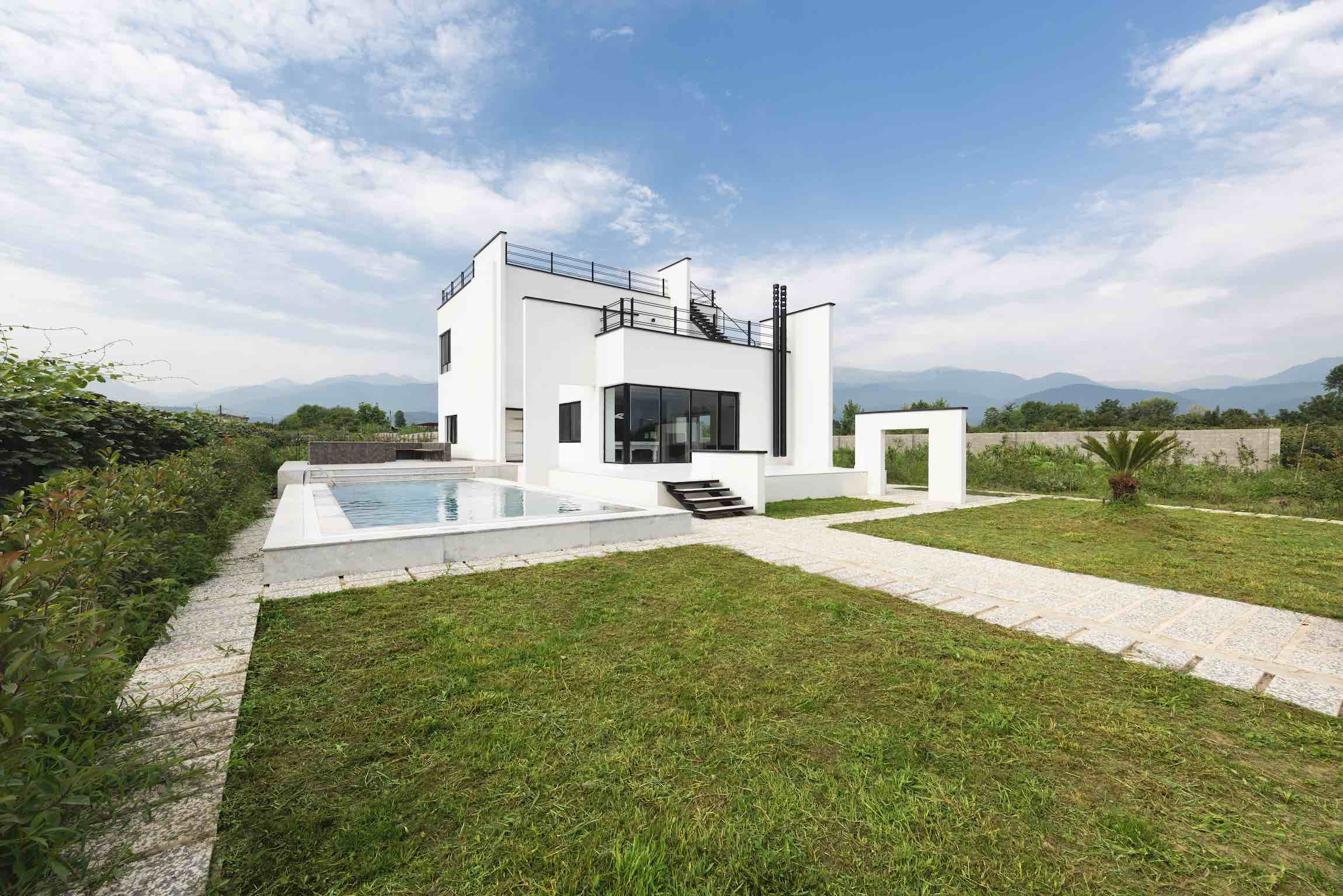 white villa with a pool at the side