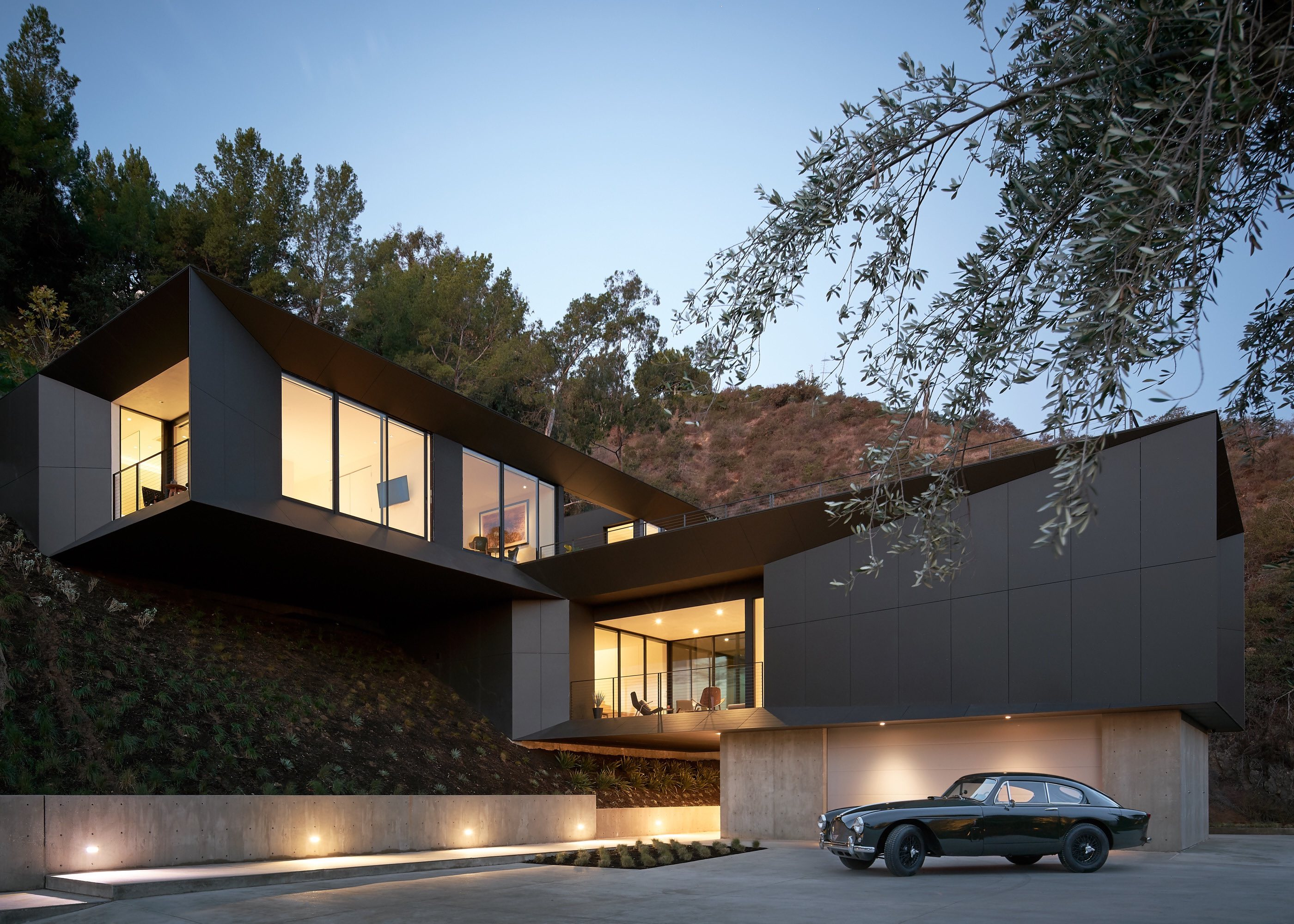 black house with illumination located on a hill