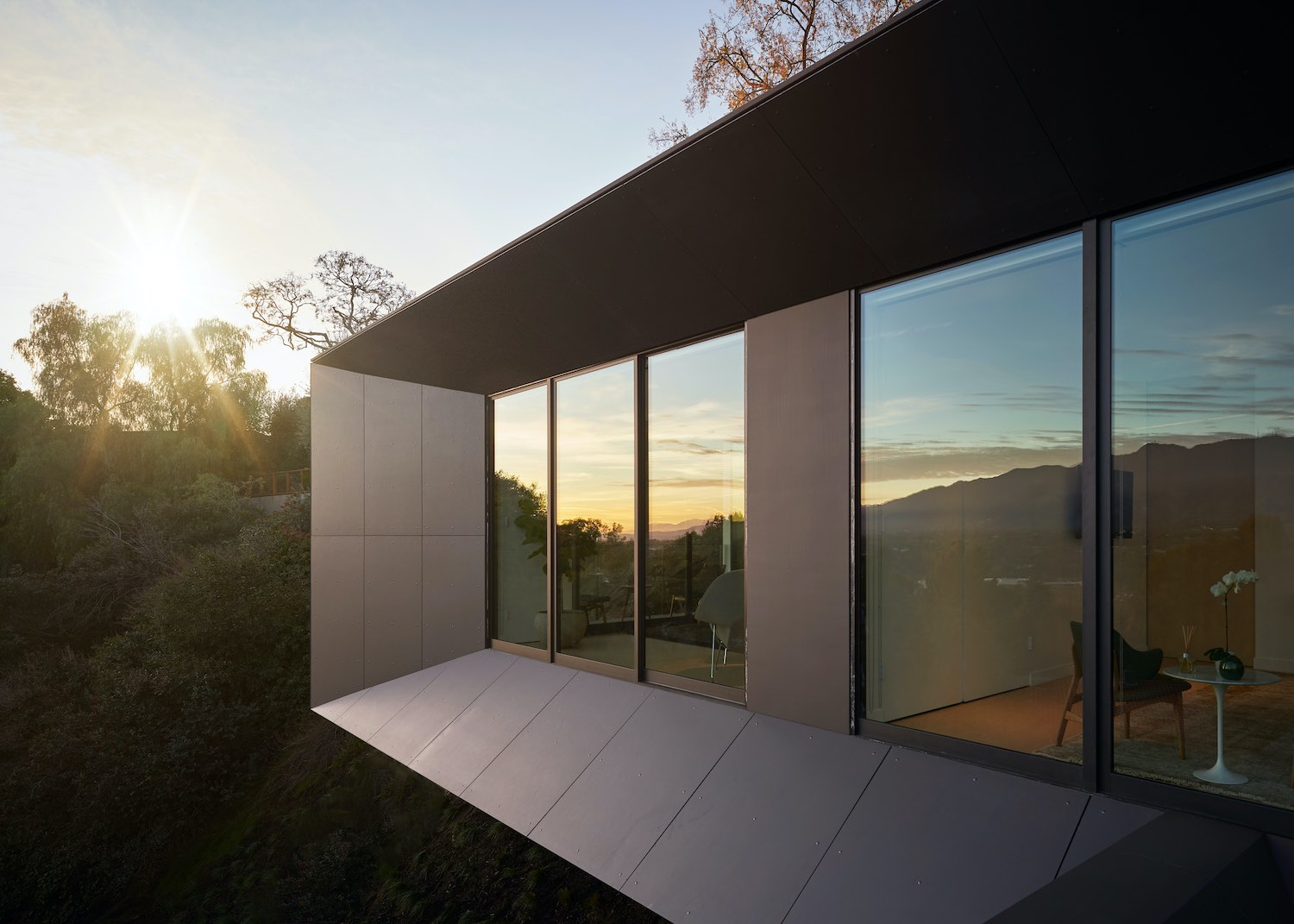 reflection of the sunset and trees on the window of the house