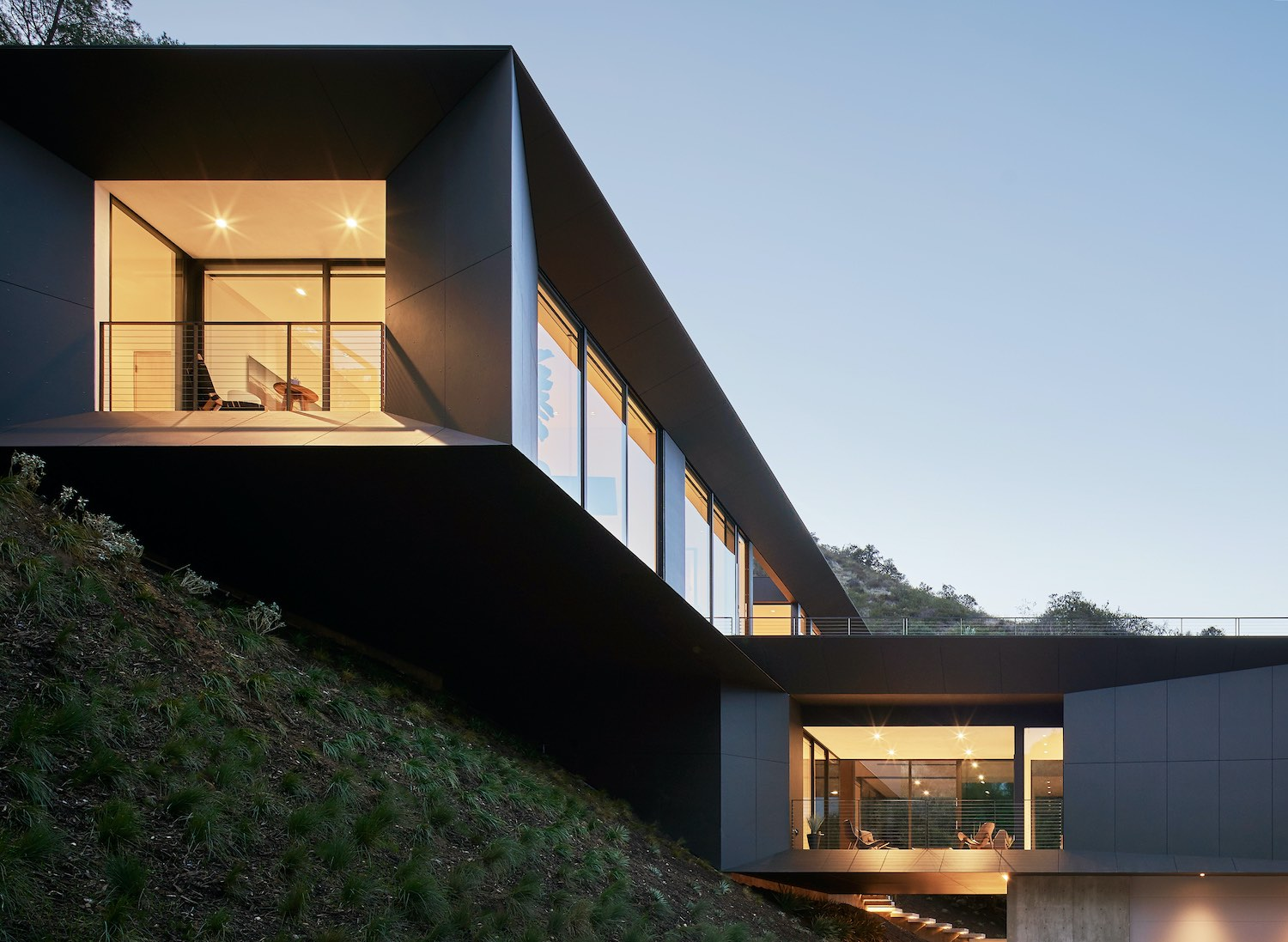 house with black metallic facade build on a hill