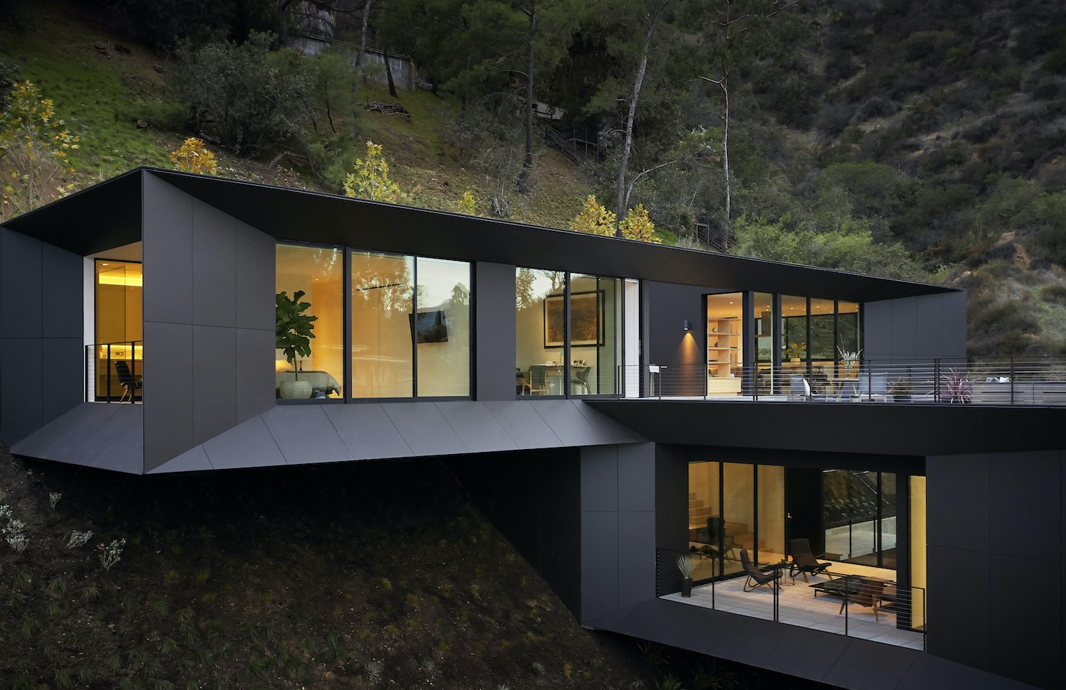 black modern house on a hill surrounded by trees