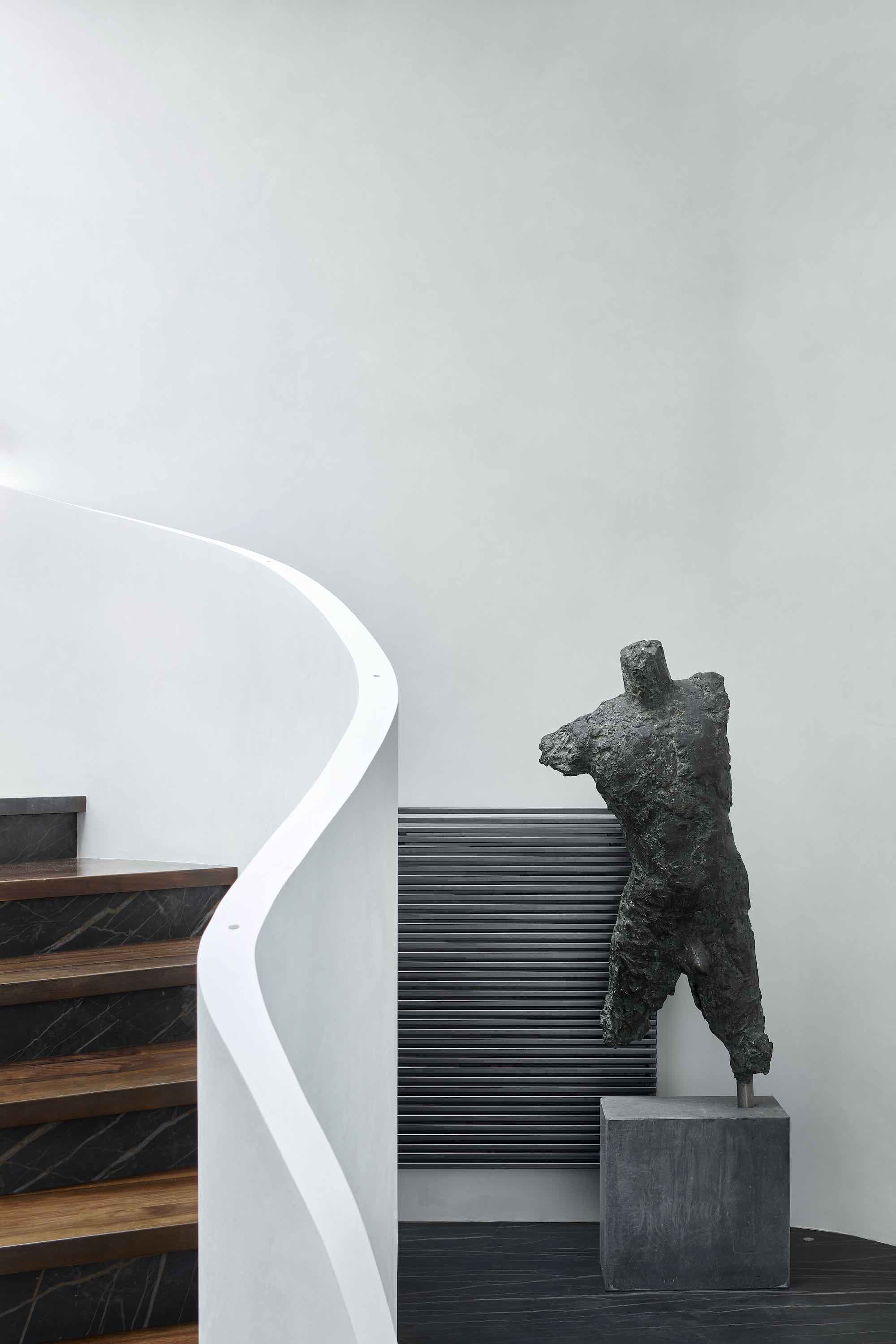 a stone sculpture of human body beside stairs