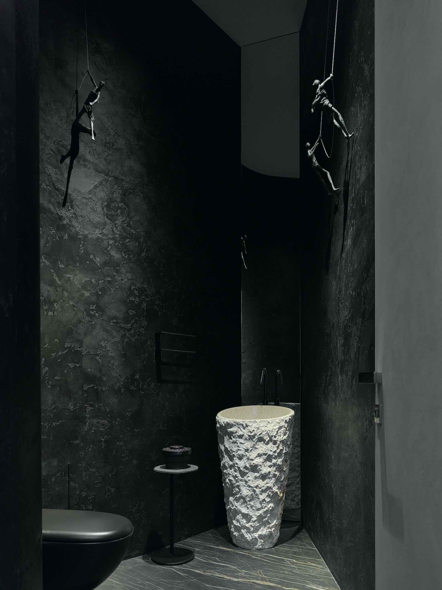 a dark toilet with washing basin made of stone
