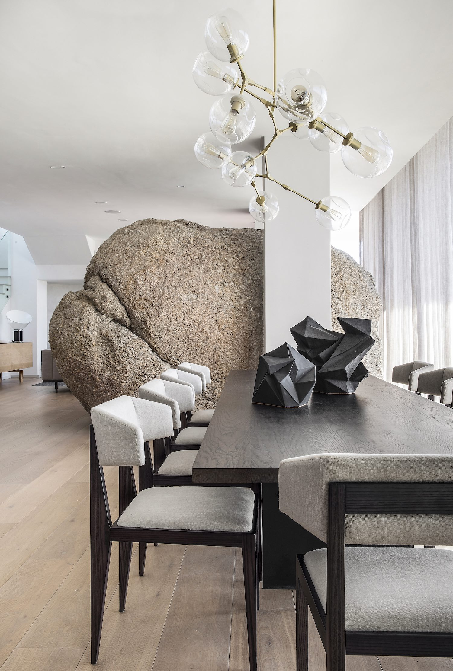 A HUGE ROCK INSIDE THE HOUSE NEAR THE DINING TABLE