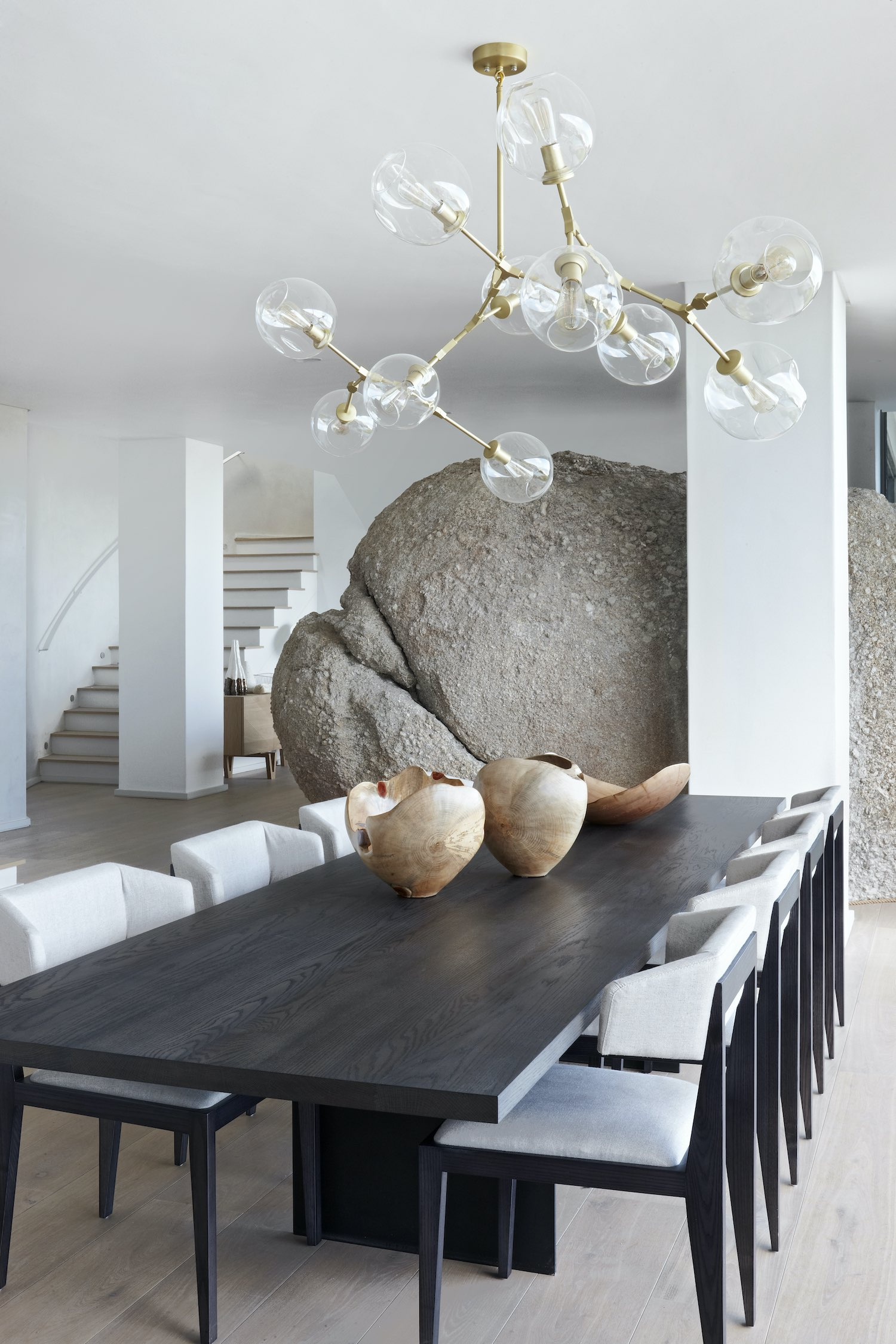 pendant lamp hanged over dining table near a rock inside the house