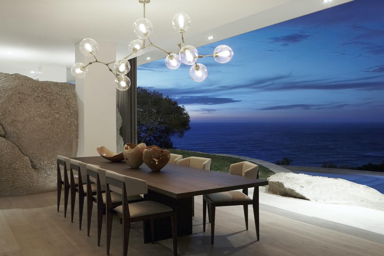 dining table near window with beautiful seaside view