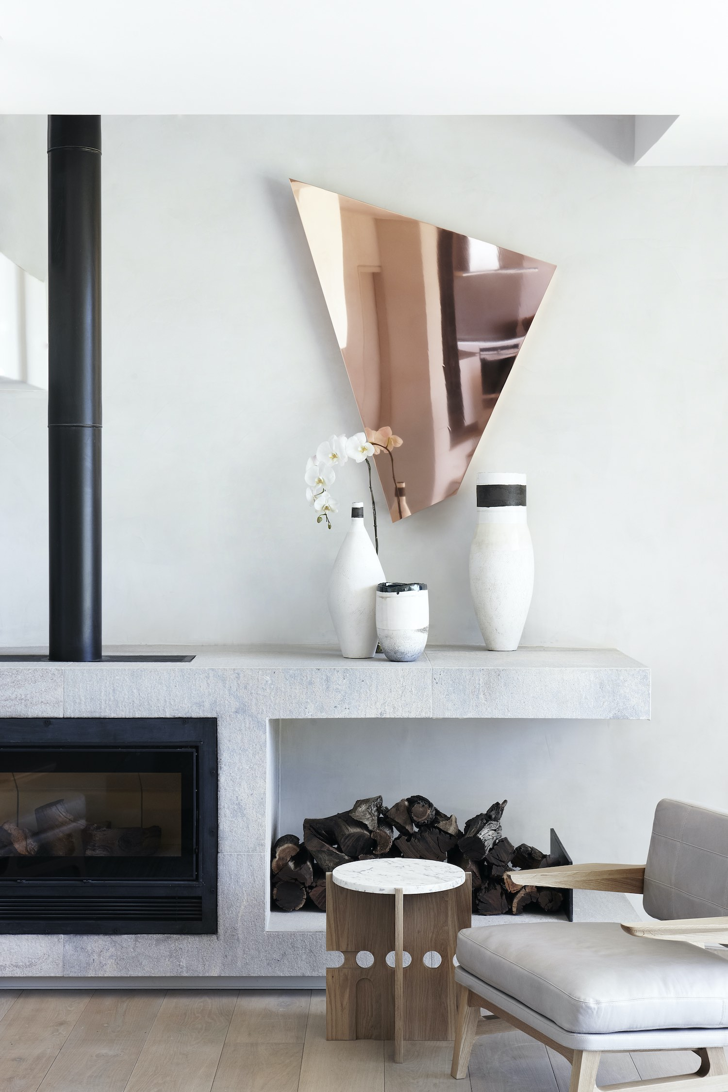 triangular mirror and flower post used as decoration near the fireplace