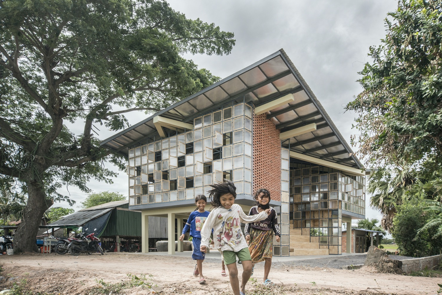 the kids are playing in front of a school surrounded by trees in Cambodia