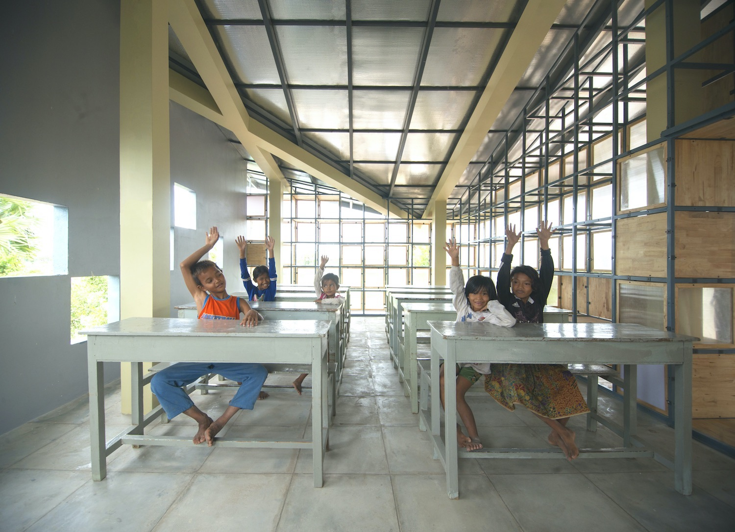 students rising their hand while sitting on school bench and desk